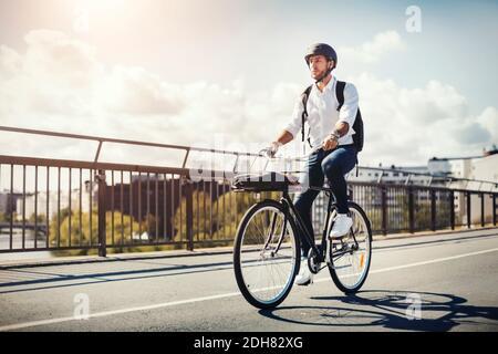 Homme d'affaires à vélo sur le pont contre le ciel