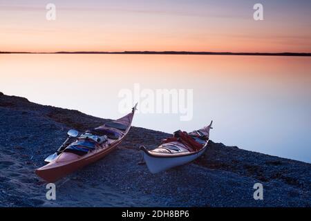 Des kayaks amarrés sur le terrain au bord d'un lac calme au coucher du soleil Banque D'Images