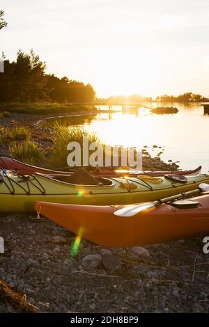 Des kayaks amarrés sur le bord du lac au coucher du soleil Banque D'Images