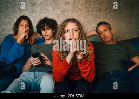 Fille priant tout en regardant le sport avec la famille à la maison