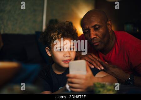 Garçon utilisant le téléphone portable par le père dans le salon à nuit