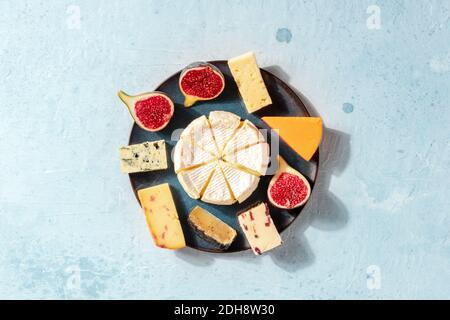Assiette de fromage, prise depuis le haut avec un endroit pour le texte. Une sélection de fromages à pâte molle et dure avec des figues