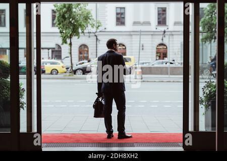 Pleine longueur d'homme d'affaires avec sac donnant sur la ville