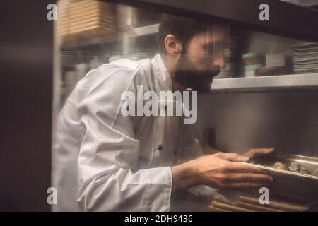 Chef cuisinier cuisant des champignons dans une cuisine commerciale