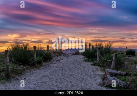 Un chemin de sable et un accès à la plage menant à travers les dunes sous un lever de soleil coloré ciel matin