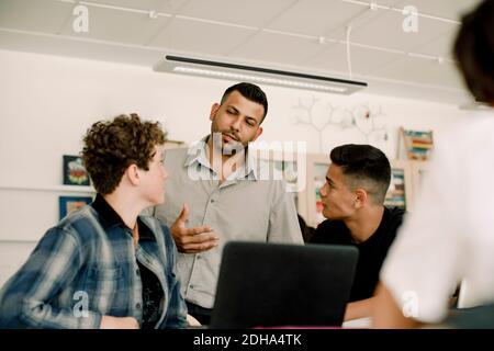 Professeur discutant avec des élèves de sexe masculin en classe
