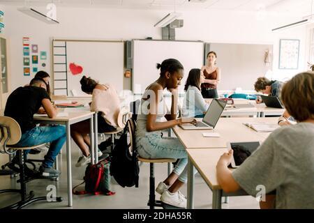 Étudiants de niveau secondaire junior étudiant pendant que la femme enseignant debout dans la salle de classe