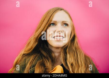 Femme adulte moyenne souriante sur fond rose