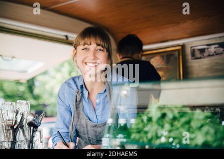 Portrait de la femme heureuse propriétaire debout dans le camion de nourriture pendant collègue travaillant en arrière-plan Banque D'Images