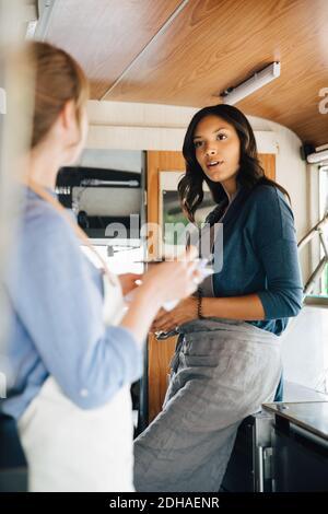 Femme propriétaire parlant à un collègue en se tenant dans un camion de nourriture Banque D'Images