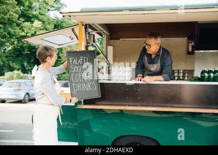 La femme a placé le tableau sur le stand de concession tandis que le collègue de travail était un homme debout dans un camion alimentaire Banque D'Images