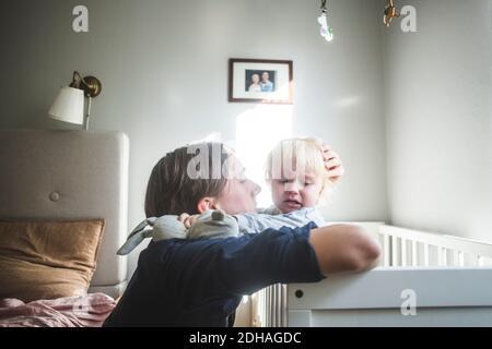 Père consolant bébé blond pleurs dans un berceau avec tendre l'amour à la maison