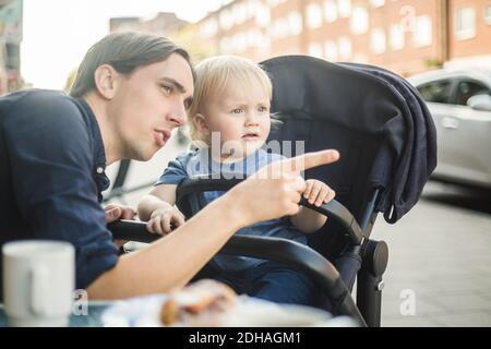 Un père qui se fait remarquer en regardant loin avec son fils au café-terrasse en ville