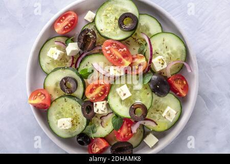 Salade grecque, une photo de gros plan en hauteur. Salade fraîche avec feta, tomates, concombres, oignons et olives