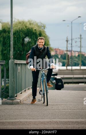 Portrait d'un homme d'affaires souriant à vélo sur le pont en ville
