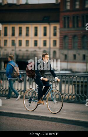 Pleine longueur d'homme d'affaires à vélo sur le pont