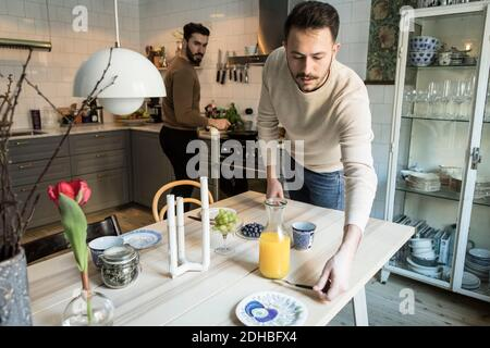 Jeune homme qui place la table pendant que le partenaire travaille en arrière-plan à cuisine