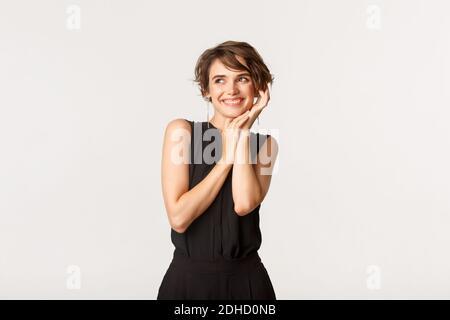 Femme flirte souriant et regardant loin tout en touchant doucement joue, rêvant de jour sur fond blanc