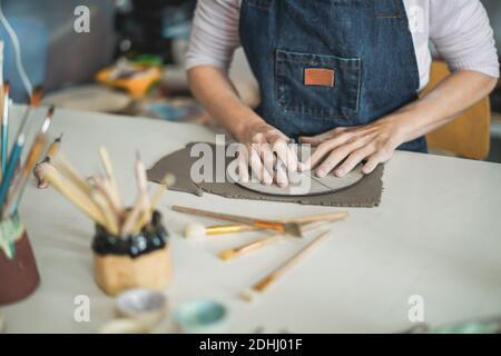 Femme faisant des objets de céramique dans le studio de poterie créative - Art Et le concept de l'atelier - concentrez-vous sur les mains libres