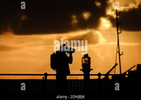 Un photographe capture le calme avant la tempête Alex, alors que le soleil se lève derrière le phare du port de Penzance le premier jour d'octobre.
