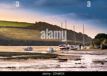 Lumière du soir sur des bateaux amarrés et bannis sur la rive de la rivière Gannel à marée basse à Newquay, en Cornouailles.