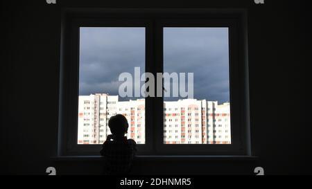 Un enfant solitaire regarde par la fenêtre de sa maison dans un appartement.