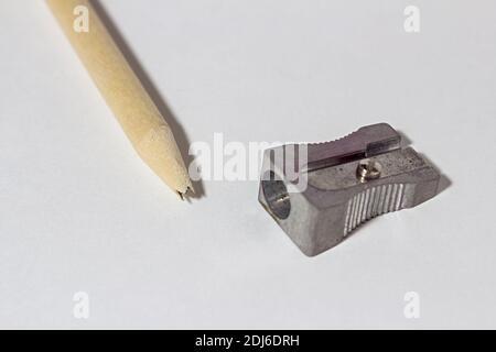 Crayon cassé avec taille-crayon métallique, tige de plomb cassée et copeaux sur fond de papier blanc