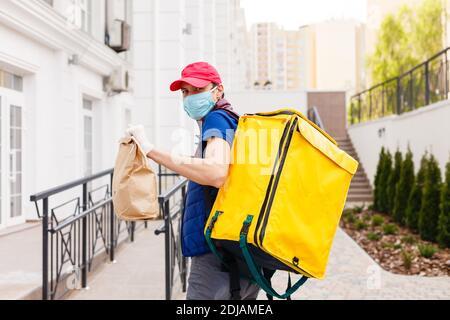 Portrait of a smiling man standing livraison avec sac à dos thermo jaune pour la livraison de nourriture dans la rue en plein air