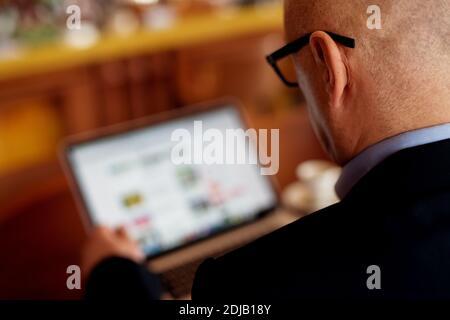 Gros plan d'un homme d'affaires professionnel mature en costume à l'aide d'un ordinateur portable.