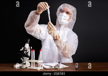 un scientifique professionnel fait des recherches et des expériences pour trouver des médicaments pour traiter le covid-19 en laboratoire, isolé sur fond noir