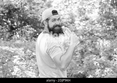 Hydrate ou mourir. Hipster brutal en forêt. Découvrez de nouveaux endroits. Temps pour pique-niquer. Guy boit de l'eau. Homme barbu en cap. Vacances d'été en camping. Homme randonnée. Homme envie d'avoir soif.