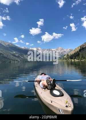 Femme couché sur kayak dans le lac contre les montagnes