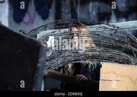 Portrait d'une jeune femme regardant à travers le fil barbelé