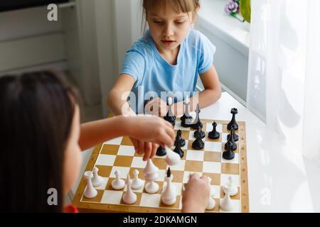 Mignon deux enfants jouant aux échecs à la maison