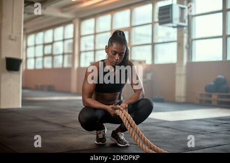 Mettre en forme une jeune femme indienne dans des vêtements de sport qui se croque dans une salle de sport et de regarder épuisé après un entraînement avec des cordes de combat Banque D'Images