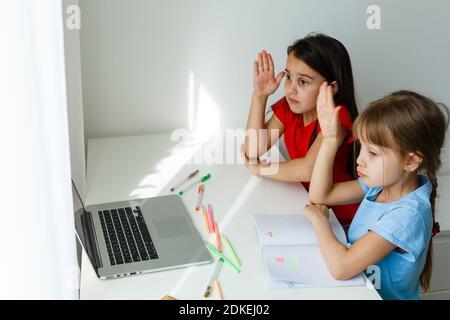 Apprendre à la maison, concept enfant école à la maison. Les petits enfants étudient l'apprentissage en ligne à la maison avec un ordinateur portable. Concept de quarantaine et de distanciation sociale. Banque D'Images