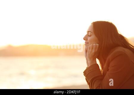 Profil d'une femme avec les yeux fermés au coucher du soleil relaxant l'esprit sur la plage en hiver