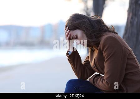 Profil d'une triste femme se plaignant assise sur un banc en hiver sur la plage