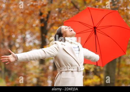 Bonne mode femme adulte avec parapluie célébrant l'automne des bras étirements dans un parc