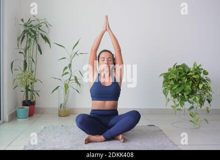 Jeune femme faisant du yoga sur le sol à la maison