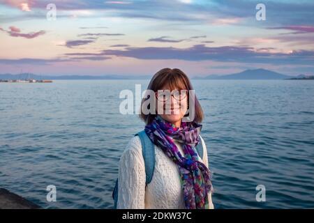 Femme mûre et gaie avec des lunettes portant un chandail blanc et une écharpe colorée souriant près de la mer derrière elle en Grèce. Concept de bonheur.