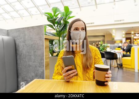 Brunette bonne jeune femme dans un masque de protection avec une tasse de café assis à une table dans le centre commercial ou le café. Couleurs jaune et gris.