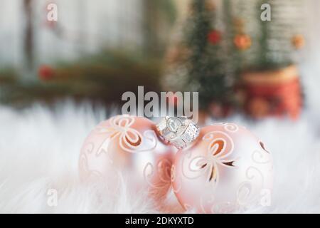 Deux décorations de Noël roses couchés sur un tapis blanc. Mise au point sélective avec des arbres de Noël flous en arrière-plan.