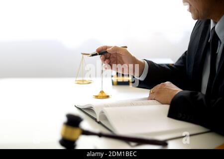 Section médiane d'un avocat tenant Pen assis à son bureau