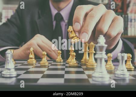 Jeu d'échecs sur le plateau d'échecs derrière l'arrière-plan homme d'affaires. Concept d'affaires pour présenter l'information financière et l'analyse de stratégie de marketing. Objectif d'investissement dans l'économie mondiale et le commerce numérique.