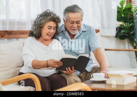 Couple asiatique grand-parent assis et lisant le livre avec le sentiment heureux dans la maison, la vie longue et la société âgée, la famille chaleureuse et le bonheur, l'épidémie de covid19 et le concept de distanciation sociale