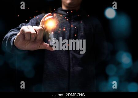 Homme d'affaires tenant une ampoule lumineuse avec une lumière orange . Concept de nouvelle idée d'entreprise créative. Banque D'Images