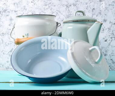 Beaucoup de plats émaillés sur une table bleue sur un fond de mur en béton blanc. Batterie de cuisine de style rétro Banque D'Images