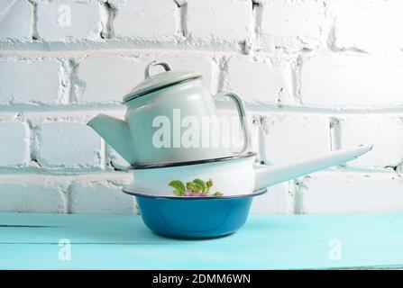 Beaucoup de plats émaillés sur une table bleue contre fond de mur de brique blanche. Batterie de cuisine de style rétro Banque D'Images