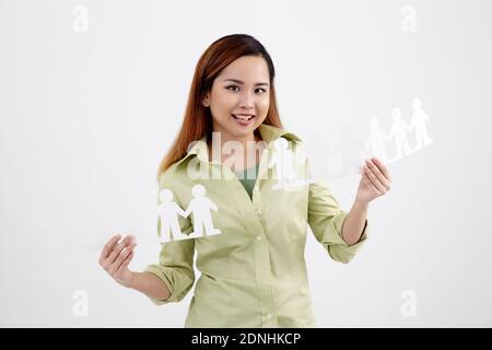 Portrait d'une jeune femme heureuse tenant des gens chaînes de papier contre fond blanc